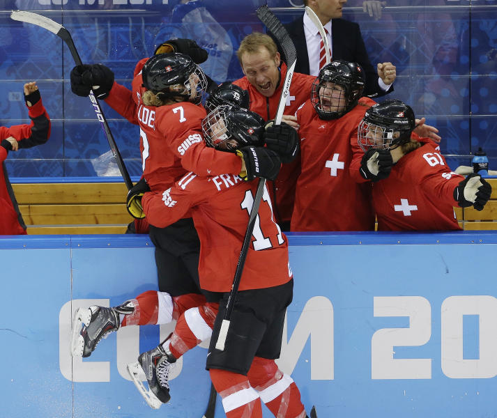 Lara Stalder of Switzerland is greeted at the bench after scoring against Russia during the 2014 Winter Olympics women's ice hockey quarterfinal game at Shayba Arena, Saturday, Feb. 15, 2014, in Sochi, Russia. Switzerland defeated Russia 2-0. (AP Photo/Matt Slocum)