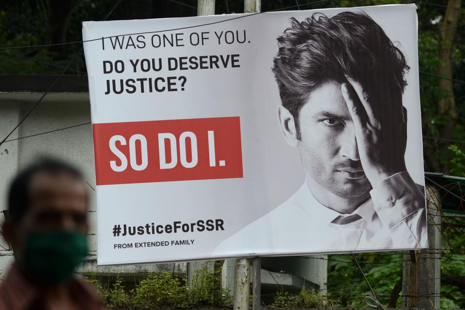 A man walks past a hoarding put up to seek justice following the suicide of actor Sushant Singh Rajput, in Mumbai on September 28, 2020. (Photo by Indranil MUKHERJEE / AFP) (Photo by INDRANIL MUKHERJEE/AFP via Getty Images)