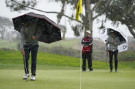 Lanto Griffin, left, moves hail from his line on the eighth green of the South Course during the second round of the Farmers Insurance Open golf tournament at Torrey Pines, Friday, Jan. 29, 2021, in San Diego. (AP Photo/Gregory Bull)