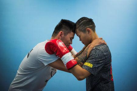 Huang Wensi and her assistant coach stand as the coach says a few motivational words before a match in Taipei, Taiwan, September 26, 2018. REUTERS/Yue Wu