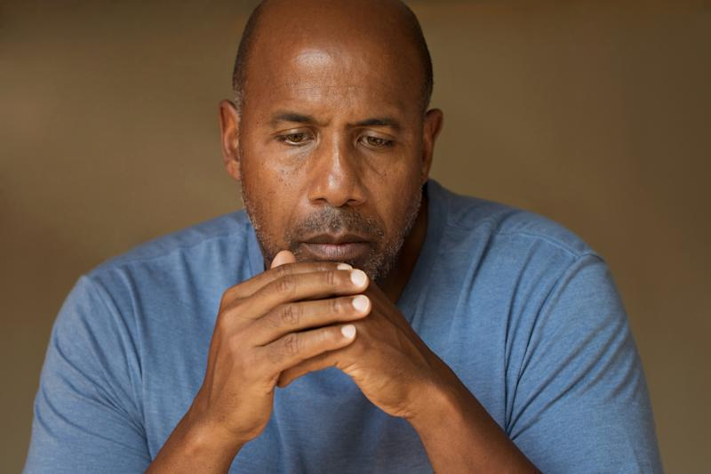 A sullen-looking man, with his hands clasped in front of him, wearing a blue shirt against a brown background.