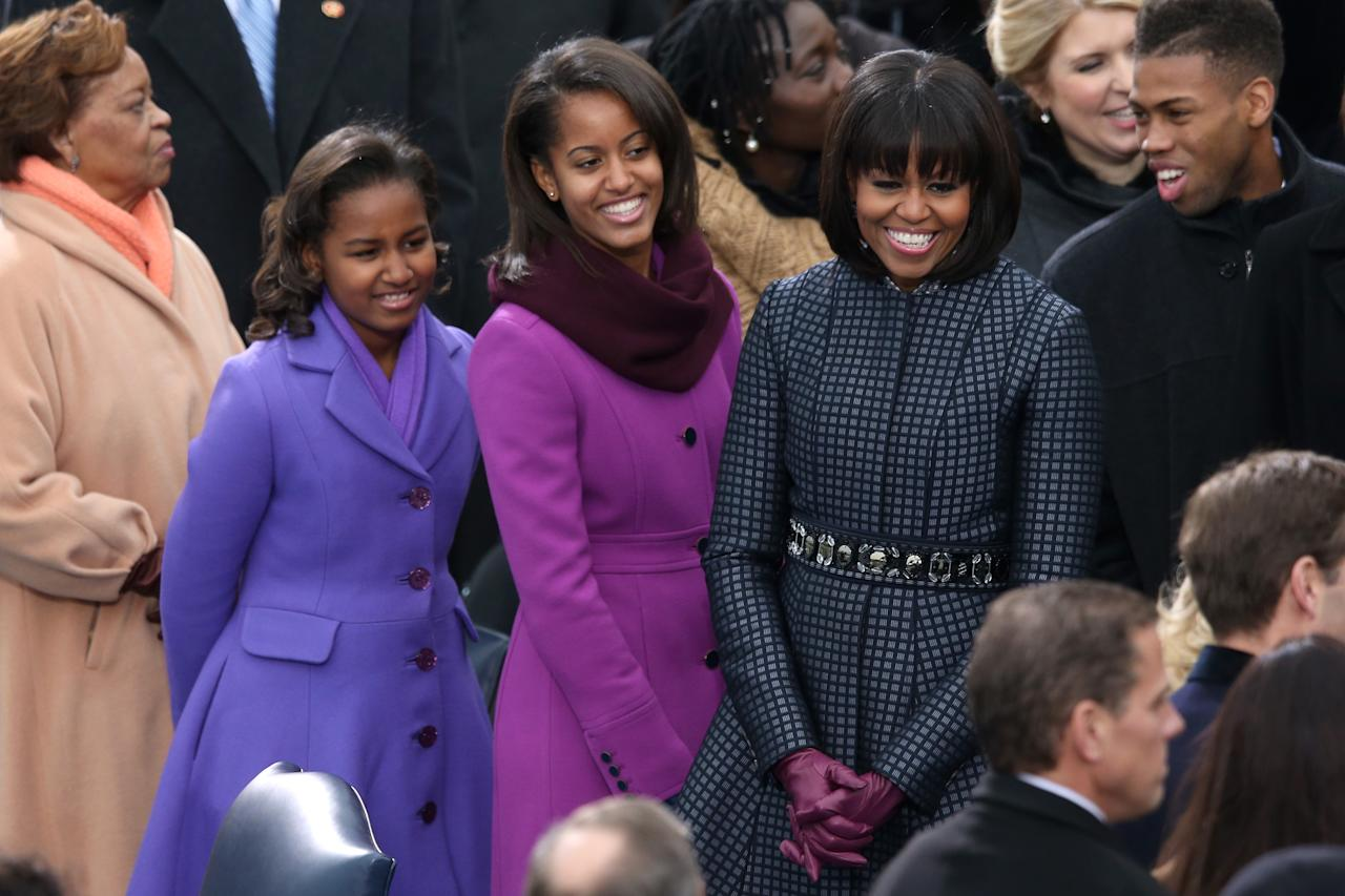 First lady Michelle Obama and daughters, Sasha Obama and Malia Obama arrive during the presidential inauguration on the West Front of the U.S. Capitol January 21, 2013 in Washington, DC.   Barack Obama was re-elected for a second term as President of the United States.  (Photo by Mark Wilson/Getty Images)
