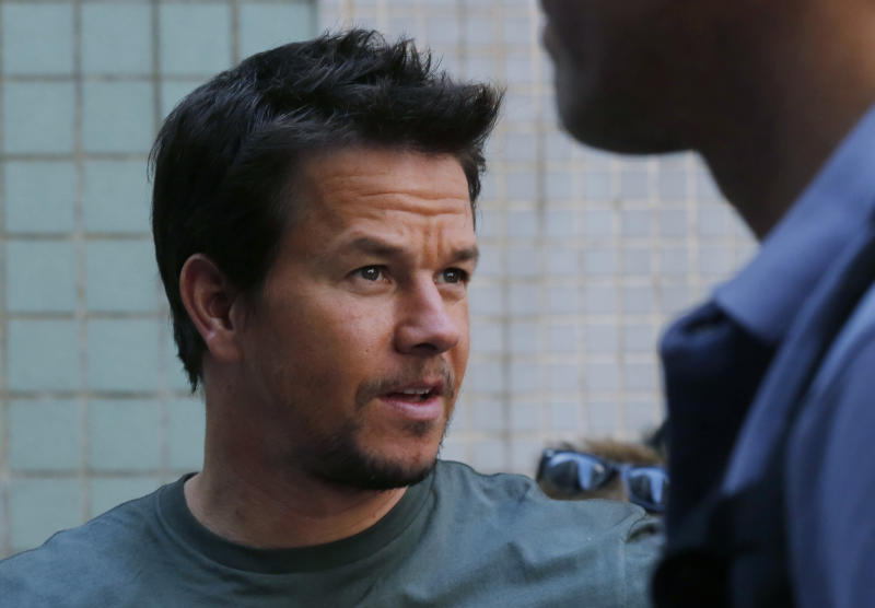 """American actor Mark Wahlberg, right, chats with film crew members before filming his latest movie """"Transformers 4: Age of Extinction"""" in Hong Kong Friday, Oct. 18, 2013. Hollywood director Michael Bay was attacked on Thursday and slightly injured on the set of the fourth installment of the """"Transformers"""" movie series filming in Hong Kong, police said. The spokeswoman said Bay suffered a minor injury to his face but declined medical treatment. (AP Photo/Kin Cheung)"""