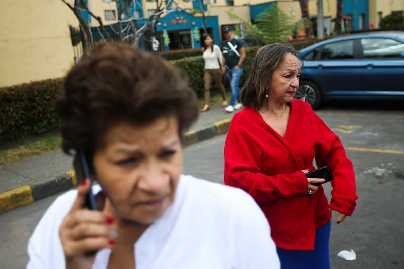 People react after an earthquake quake in Bogota