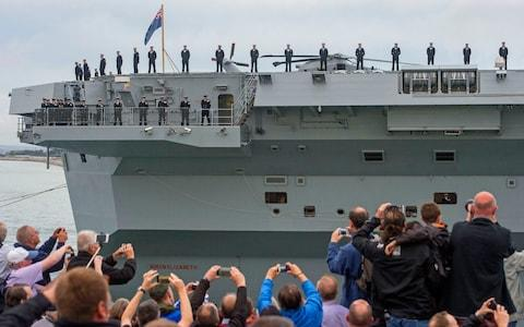 HMS Queen Elizabeth crew members watch as crowds line Portsmouth Harbour - Credit: Victoria Jones/PA