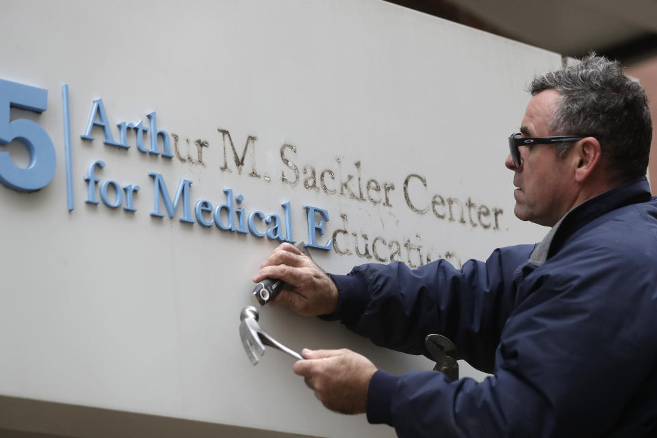 FILE - In this Thursday, Dec. 5, 2019 file photo, Worker Gabe Ryan removes a sign that includes the name Arthur M. Sackler at an entrance to Tufts School of Medicine, Thursday, Dec. 5, 2019, in Boston. The end of the Purdue Pharma bankruptcy case has left a bitter taste for those who wanted to see more accountability for the Sackler family. They will pay more than $4 billion under the settlement but also will escape any future liability over the nation's opioid crisis. The question at the heart of the upcoming appeals is whether it's appropriate for a wealthy family that did not itself file for bankruptcy to get such a broad protection given its role in a crisis that continues take a deadly toll across America. (AP Photo/Steven Senne, File)