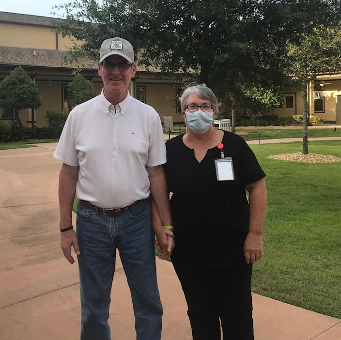 Steve and Mary Daniel outside Rosecastle at Deerwood, a memory-care center. Mary Daniel took a job as a dishwasher there so she could spend time with her husband, a resident who's been under lockdown since March.