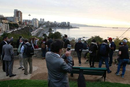 People stand and watch the ocean on Cerro Castillo hill, after a mass evacuation of the entire coastline during a tsunami alert after a magnitude 7.1 earthquake hit off the coast in Vina del Mar, Chile.