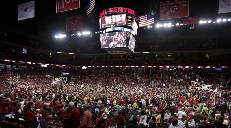 Fans rush the court after Wisconsin defeated Michigan 65-62 in an NCAA college basketball game Saturday, Feb. 9, 2013, in Madison, Wis. (AP Photo/Andy Manis)