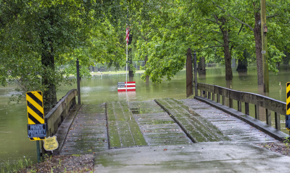A wooden bridge leads to a flooded area along Bluff Road Tuesday, May 18, 2021, in Ascension Parish, La. Heavy rains have swept across southern Louisiana, flooding homes, swamping cars and closing a major interstate. (Bill Feig/The Advocate via AP)