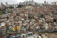 Workers paint the facades of residences in the Paraisopolis favela, as part of the community's centennial celebration, in Sao Paulo, Brazil, Thursday, Sept. 16, 2021. One of the largest favela's in Brazil, home to tens of thousands of residents in the country's largest and wealthiest city, Paraisopolis is grappling with crime and a pandemic that have challenged daily life for many who live there, but organizers say its people have built a vibrant community and are launching a 10-day celebration of its achievements. (AP Photo/Andre Penner)