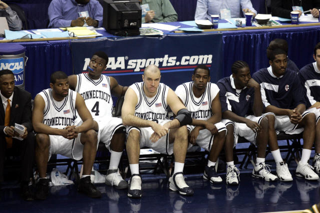 FILE - In this March 26, 2006, file photo, dejected Connecticut players watch near the end of overtime in a game against George Mason during the fourth round of the NCAA college basketball tournament in Washington. George Mason defeated Connecticut, 86-84 to advance to the Final Four. (AP Photo/Lawrence Jackson, File)