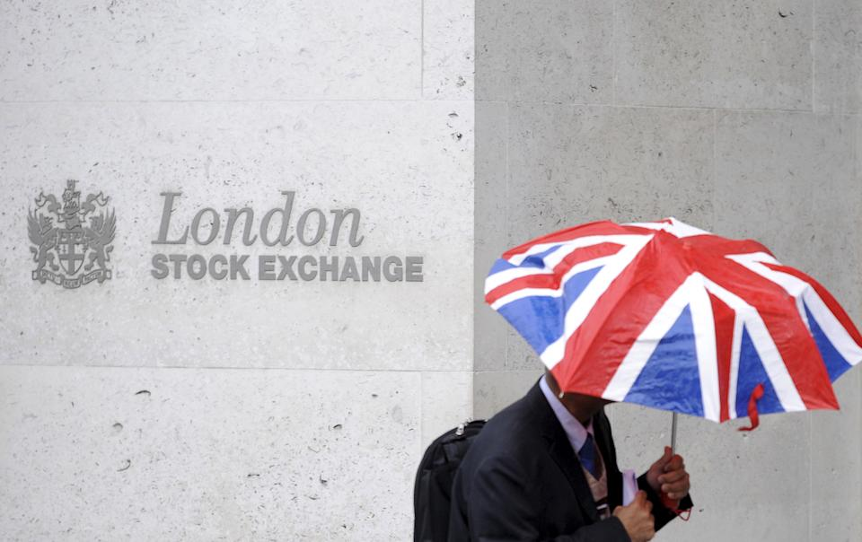 A worker shelters from the rain as he passes the London Stock Exchange in the City of London at lunchtime October 1, 2008.  REUTERS/Toby Melville/File Photo         GLOBAL BUSINESS WEEK AHEAD PACKAGE - SEARCH 'BUSINESS WEEK AHEAD APRIL 25'  FOR ALL IMAGES