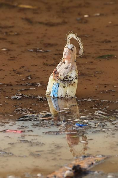 A picture taken on October 4, 2015, shows a statue of the Virgin Mary (our Lady of Lourdes), floating among waste in a flooded street, in Mandelieu-la-Napoule, southeastern France (AFP Photo/Boris Horvat)