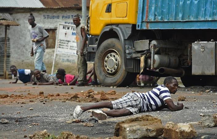 Protestors opposed to a third term for the Burundian President take cover from live fire by police in the Musaga neighborhood of Bujumbura on May 20, 2015 (AFP Photo/Carl de Souza)