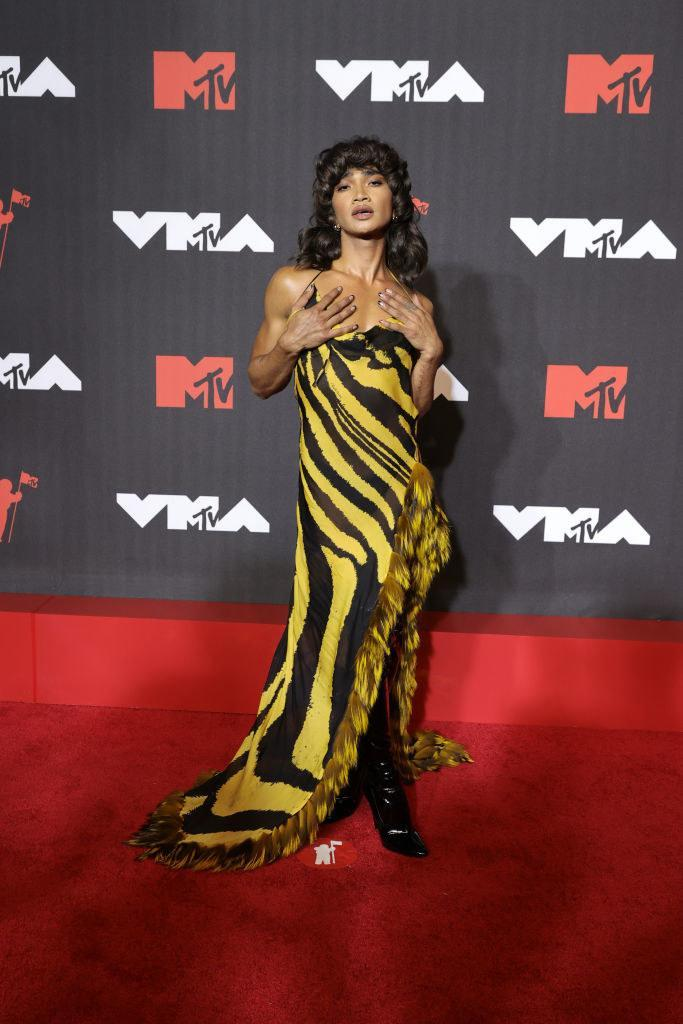 Bretman posing in a striped gown and boots