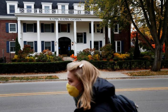 FILE PHOTO: A woman wearing a protective face mask walks past a sorority house on the University of Michigan campus in Ann Arbor