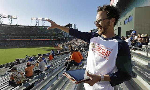 In this photo taken Friday, July 25, 2014, Joel Carben gestures while standing in the bleacher seats in right field prior to a baseball game between the Los Angeles Dodgers and the San Francisco Giants at AT & T Park in San Francisco. Carben has designed mobile foul ball tracking system software designed to increase a fan's chances of catching a foul ball at baseball games. (AP Photo/Ben Margot)
