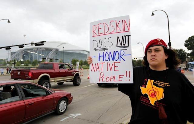 "Native American Steve Morales, of Dallas, holds up a sign that reads ""Redskin does not honor Native People"", as he joins others in protest outside of an NFL football game between the Washington Redskins and Dallas Cowboys, Sunday, October 13, 2013, in Arlington, Texas. (AP Photo/LM Otero)"