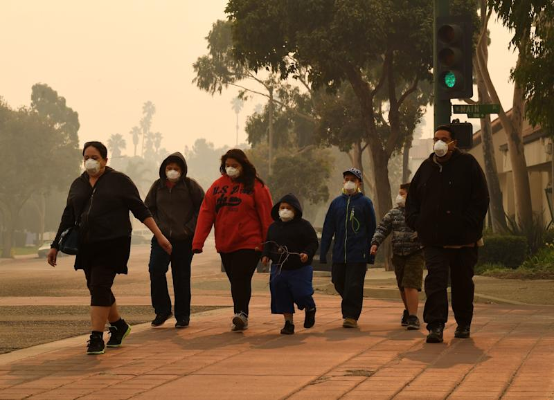 A family wears masks as they walk through the smoke-filled streets after the Thomas fire swept through Ventura County. (MARK RALSTON via Getty Images)