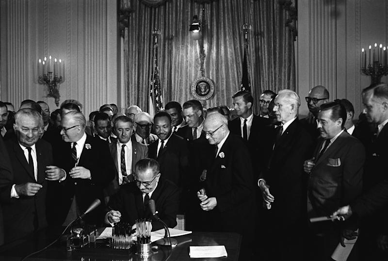 Then-President Lyndon B. Johnson signs the 1964 Civil Rights Act, which established a Justice Department office to provide confidential services to ease tensions in communities facing racial and other conflicts. The Trump administration's budget proposal would eliminate the office. (Photo 12/UIG via Getty Images)