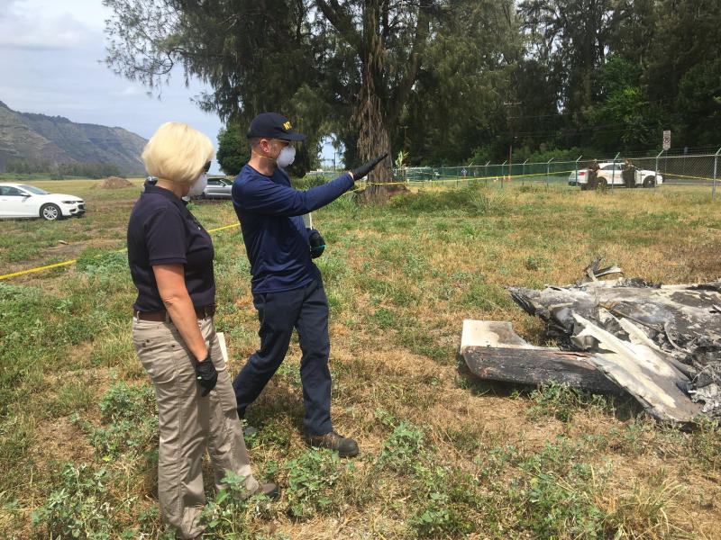 This Sunday, June 23, 2019, photo released by the National Transportation Safety Board shows NTSB investigator Eliott Simpson briefing NTSB Board Member Jennifer Homendy at the scene of the Hawaii skydiving crash in Oahu, Hawaii. No one aboard survived the crash, which left a small pile of smoky wreckage near the chain link fence surrounding Dillingham Airfield about an hour north of Honolulu. (National Transportation Safety Board via AP)