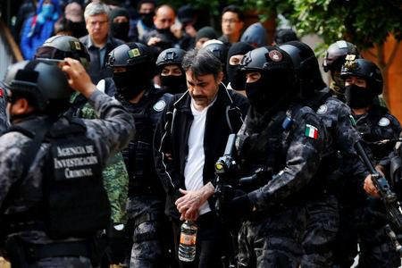 """Accused drug kingpin Damaso Lopez, nicknamed """"The Graduate"""",  is escorted by police officers in Mexico City"""