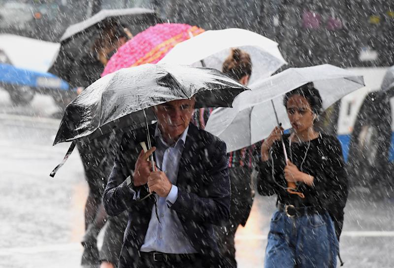 Pedestrians hold umbrellas during wet weather in Sydney, Friday, February 7, 2020.