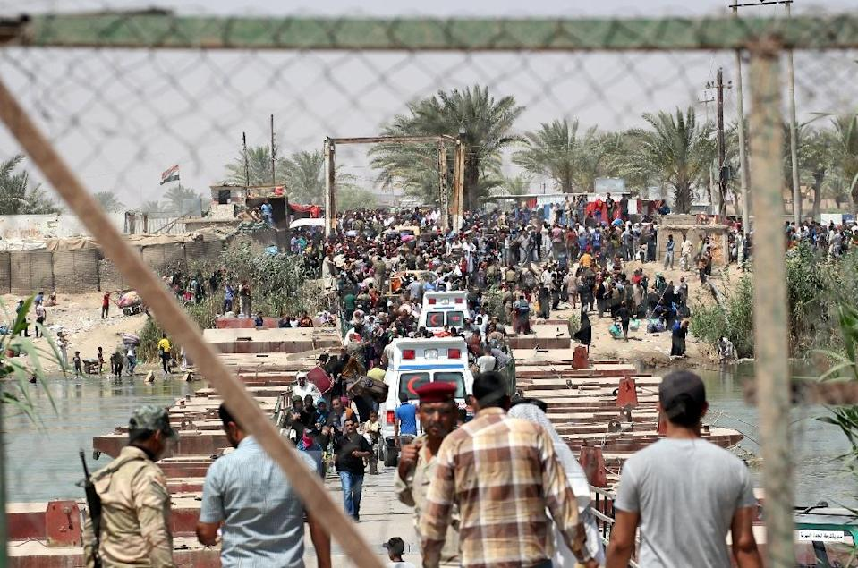 Iraqi security forces stand guard as residents from the city of Ramadi, who fled their homes as Islamic State group militants tightened their siege wait to cross Bzeibez bridge on May 20, 2015 (AFP Photo/Sabah Arar)