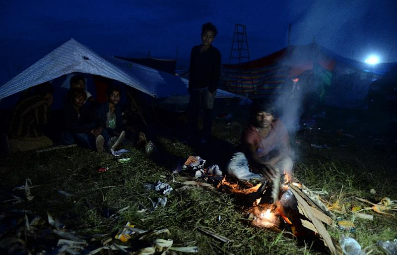 Nepalese people light fires to keep themselves warm as they spend a night in the open in Kathmandu on April 27, 2015 (AFP Photo/Prakash Singh)