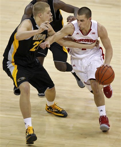 Milwaukee's J.J. Panoske, left, reaches for the ball as Wisconsin's Ben Brust drives during the first half of an NCAA college basketball game Saturday, Dec. 22, 2012, in Madison, Wis. (AP Photo/Andy Manis)