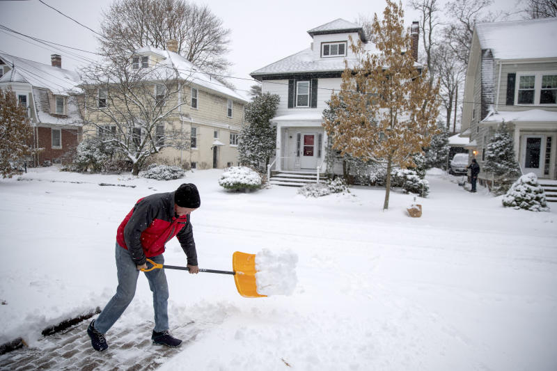 Paul Mooney shovels snow outside his home, Tuesday, Dec. 3, 2019, in Providence, R.I. The National Weather Service issued a winter storm warning Tuesday for coastal areas of Massachusetts, New Hampshire and Maine and a winter weather advisory for southeastern Massachusetts and Rhode Island.  (AP Photo/David Goldman)