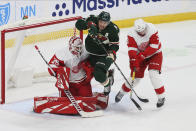 Minnesota Wild's Zach Parise, center, jumps to clear the way for a shot as Detroit Red Wings' goalie Jimmy Howard, left, defends in the first period of an NHL hockey game Wednesday, Jan. 22, 2020, in St. Paul, Minn. (AP Photo/Jim Mone)