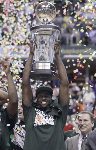 Michigan State forward Draymond Green holds up the Big Ten trophy after an NCAA college basketball game against Ohio State in the final of the conference's men's tournament in Indianapolis, Sunday, March 11, 2012. Michigan State won 68-64. At right is Michigan State coach Tom Izzo. (AP Photo/Michael Conroy)