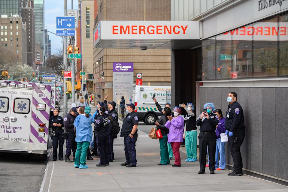 NEW YORK, NY - APRIL 04: Medical personnel are seen outside NYU Langone Health hospital as people applaud to show their gratitude to medical staff and essential workers working on the front lines of the coronavirus pandemic as the country works to stop the spread of COVID-19 on April 4, 2020 in New York City. The coronavirus (COVID-19) pandemic has spread to at least 180 countries and territories across the world, claiming over 60,000 lives and infecting hundreds of thousands more. (Photo by Noam Galai/Getty Images)