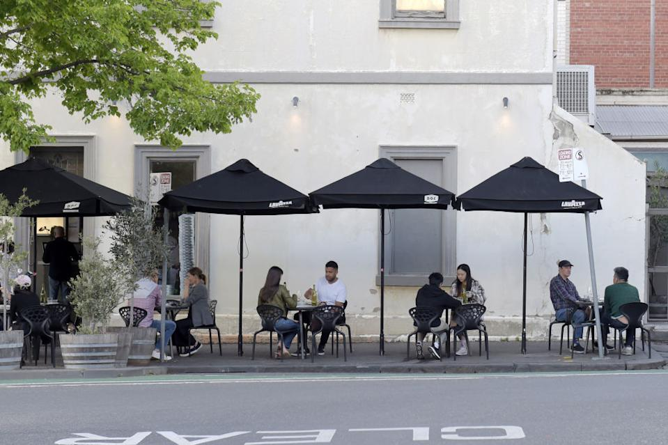Customers sit at socially distanced tables outside a restaurant in the Carlton suburb of Melbourne.