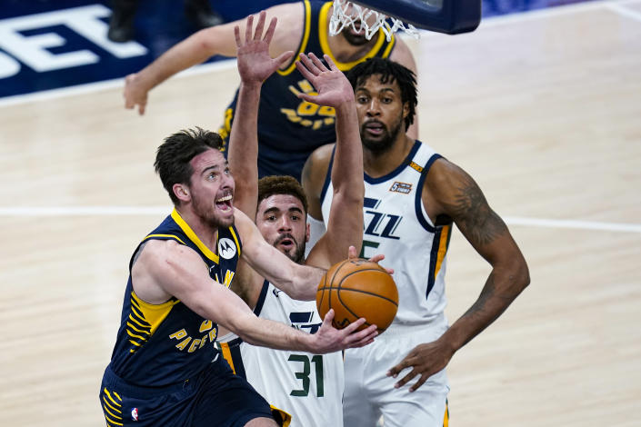 Indiana Pacers guard T.J. McConnell (9) shoots in front of Utah Jazz forward Georges Niang (31) during the second half of an NBA basketball game in Indianapolis, Sunday, Feb. 7, 2021. (AP Photo/Michael Conroy)