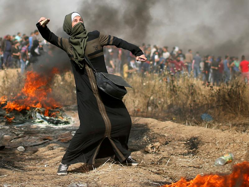 A girl hurls stones during clashes with Israeli troops at a protest where Palestinians demand the right to return to their homeland, at the Israel-Gaza border: Reuters
