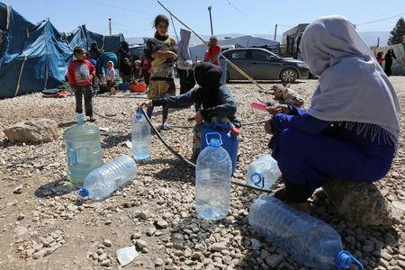Syrian refugees fill containers and bottles with water at a makeshift settlement in Bar Elias town, in the Bekaa valley, Lebanon March 27, 2017. Picture taken March 27, 2017. REUTERS/Aziz Taher