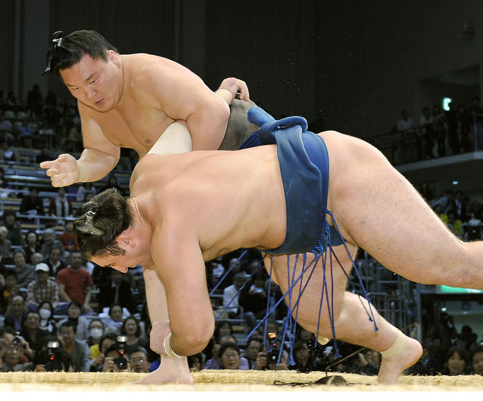 Mongolian-born grand champion Hakuho throws Georgian Tochinoshin to extend his winning streak to 63 at the Kyushu Grand Sumo Tournament in Fukuoka, southwestern Japan, on Nov. 15, 2010. Hakuho is retiring at age 36, marking an end of an era in the history of Japanese traditional sport. The Mongolian-born Yokozuna, or grand champion, Hakuho has won a record 45 tournaments, including 16 perfect victories, which is also a record. (Kyodo News via AP)