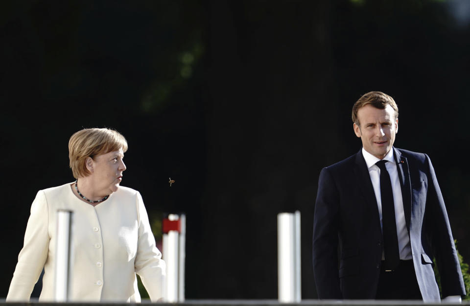 German Chancellor Angela Merkel, left and French President Emmanuel Macron walk on the way to a press conference after their talk, at Meseberg Castle, the German government's guest house in Meseberg, Germany, Monday, June 29, 2020. Merkel met Monday with French President Emmanuel Macron for talks as Germany prepares to take over the European Union presidency. (Kay Nietfeld/dpa via AP)