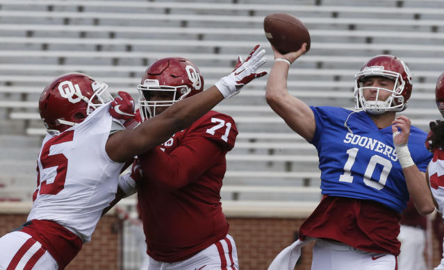 Oklahoma quarterback Austin Kendall (10) passes under pressure from linebacker Addison Gumbs (15) as offensive lineman Bobby Evans (71) blocks during the Oklahoma NCAA college football spring intra-squad game in Norman, Okla., Saturday, April 14, 2018. (AP Photo/Sue Ogrocki)