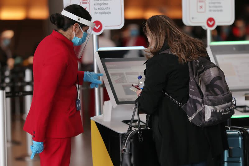 An employee of the Avianca Airlines, wearing a face shield and a protective mask, talks to a passenger at the check-in section at the El Dorado International Airport, in Bogota