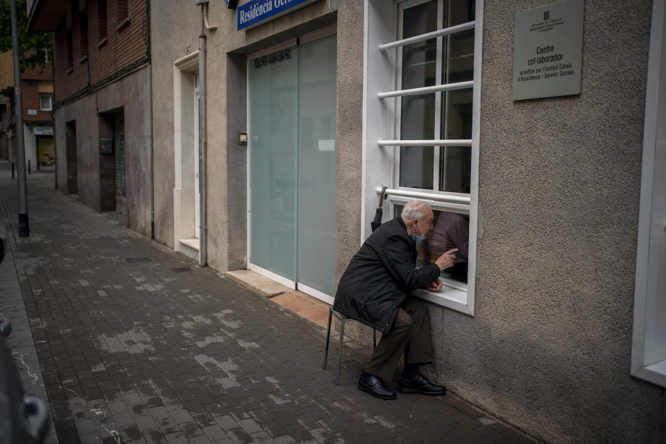 Javier Anto, 90, speaks to his wife Carmen Panzano, 92, through the window separating the nursing home from the street in Barcelona, Spain, Wednesday, April 21, 2021. Since the pandemic struck, a glass pane has separated _ and united _ Javier and Carmen for the first prolonged period of their six-decade marriage. Anto has made coming to the street-level window that looks into the nursing home where his wife, since it was closed to visits when COVID-19 struck Spain last spring. (AP Photo/Emilio Morenatti)