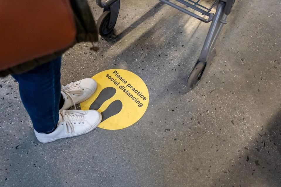 Person standing near social distancing sign