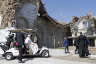 Pope Francis, sitting in a cart, is shown the devastation of the Syriac Catholic Al-Tahera church near Hosh al-Bieaa Church Square where he led a prayer session in Mosul, Iraq, once the de-facto capital of IS, Sunday, March 7, 2021. The long 2014-2017 war to drive IS out left ransacked homes and charred or pulverized buildings around the north of Iraq, all sites Francis visited on Sunday. (AP Photo/Andrew Medichini)