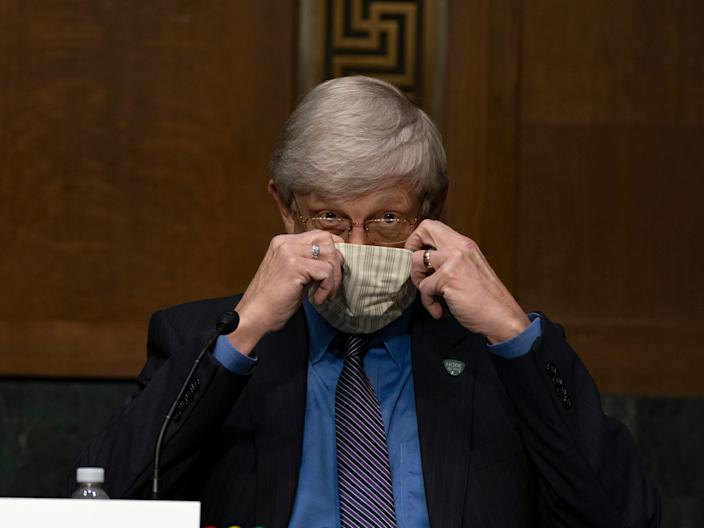 National Institutes of Health Director Dr. Francis Collins puts on his face mask after a Senate hearing.