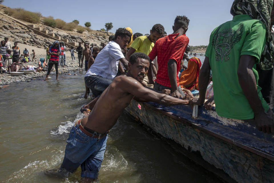 Tigray refugees who fled the conflict in the Ethiopia's Tigray ride a boat on the banks of the Tekeze River on the Sudan-Ethiopia border, in Hamdayet, eastern Sudan, Saturday, Nov. 21, 2020. The U.N. refugee agency says Ethiopia's growing conflict has resulted in thousands fleeing from the Tigray region into Sudan as fighting spilled beyond Ethiopia's borders and threatened to inflame the Horn of Africa region. (AP Photo/Nariman El-Mofty)