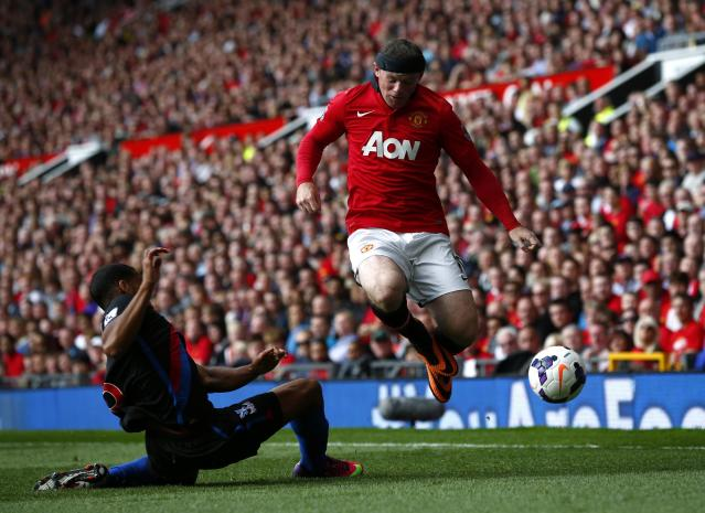 Manchester United's Rooney is challenged by Crystal Palace's Mariappa during their English Premier League soccer match at Old Trafford in Manchester, northern England