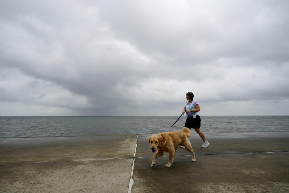 Jane McDow walks with her dog 'Duke' along the Lake Pontchartrain seawall in New Orleans, Wednesday, Oct. 28, 2020. Hurricane Zeta is expected to make landfall this afternoon as a category 2 storm. (AP Photo/Gerald Herbert)